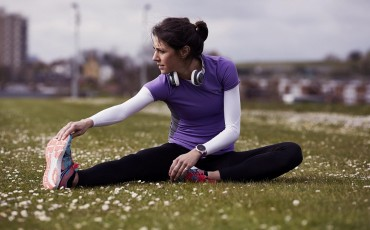 A runner stretching on the grass